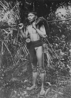 COLLECTIE_TROPENMUSEUM_Portret_van_een_Dajak_jager_op_Borneo_met_een_gevangen_zwijn_over_de_schouder_TMnr_60043389